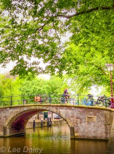 Amsterdam: Bikes, bridges and bread., Bicyclist Riding Over A Canal