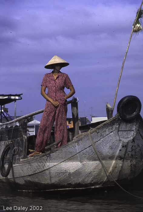 deep culture of Vietnam, Mekong River boatwoman, cruise the Might Mekong on a wooden river boat, explore small Vietnam villages, Mekong Delta.